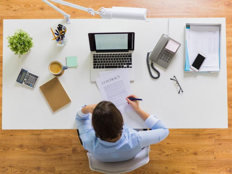 business, people and work concept - businesswoman signing contract document sitting at office table